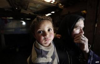 A Syrian woman carries her two-year-old grandson at a refugee camp in the village of Saadnayel in the Bekaa Valley, Lebanon, 6 March