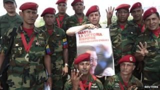 Soldiers of the military group 4F pose for a photo with a poster of Hugo Chavez outside the Military Academy, where the funeral service of Mr Chavez is being held, in Caracas on 10 March 2013