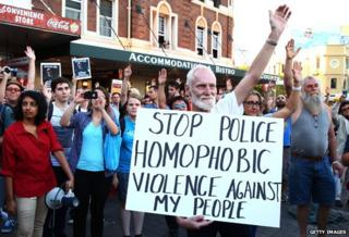 protester holding placard which reads: Stop police homophobic violence against my people
