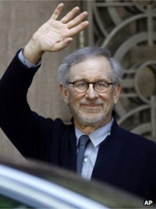 """Director Steven Spielberg waves to the media as he leaves Indian Industrialist Anil Ambani""""s office in Mumbai, India, Monday, March 11, 2013."""