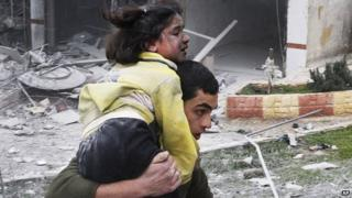 Syrian man carries his sister who was wounded in an airstrike in Aleppo, Syria, Sunday 3 February 2013