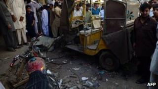 Local Pakistani residents gather at the site of the overnight bomb blast in Karachi on 15 March 2013