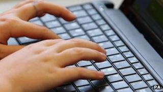 A close-up on someone's hands as they type on a laptop keyboard