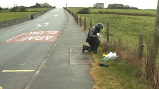 Flowers have been laid at the scene of the fatal collision near Amlwch
