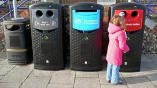 Girl placing a bottle in a recycle bin