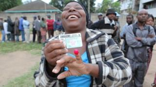 A woman shows her ink stained index finger after casting her vote during a referendum in Harare, Zimbabwe, Saturday 16 March 2013