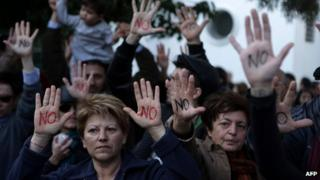 """Cypriots show their palms reading """"No"""" during a protest against an EU bailout deal"""