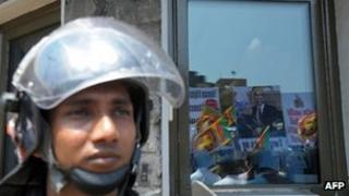 Pro-government activists are reflected in the glass of the US embassy during a protest in Colombo on March 21, 2013,