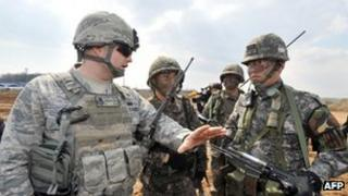 A US air force soldier, left, talks to South Korean army soldiers during an operation to guard a US airbase as part of annual joint exercises outside the airbase in Pyeongtaek, south of Seoul, 14 March 2013