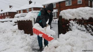 Woman shovelling snow outside her house