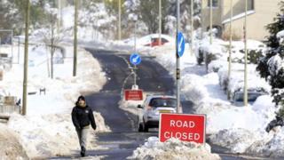 Man walks on closed road in Cargan in the Glens of Antrim
