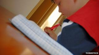 Boy writing in exercise book