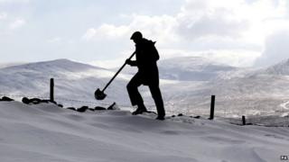 A man silhouetted against a white snowy hillside