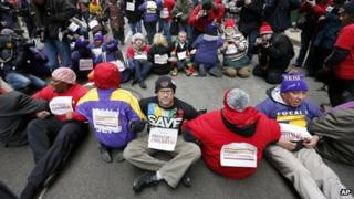 Protesters sit on LaSalle Street during an act of civil disobedience in Chicago, Illinois 27 March 2013