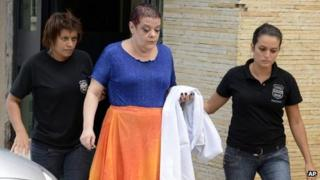 Dr Virginia Helena Soares de Souza, centre, who is charged with killing seven patients, is escorted by police officers to a temporary prison in Curitiba, Parana state, Brazil on 19 February 2013
