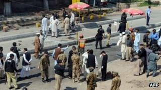 Pakistani soldiers gather at the site of a suicide attack in Peshawar on March 29, 2013.