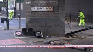 Workers clear the scene on where two men died following a police chase