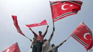 Acehnese men wave Crescent-Star flags during a rally outside Baiturrahman Grand Mosque in Banda Aceh, Aceh province, Indonesia, Monday, April 1, 2013.