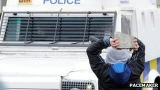 A youth throws a brick at a police vehicle