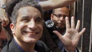"""Popular Egyptian television satirist Bassem Youssef, who has come to be known as Egypt""""s Jon Stewart, waves to is supporters as he enters Egypt""""s state prosecutors office"""