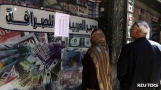 People look at the currency exchange rates outside of an exchange bureau in central Cairo