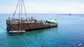This undated handout photo released on 30 March 2013 shows the stern of the USS Guardian before being lifted by a boat crane at Tubbataha reef, in Palawan Island, Philippines