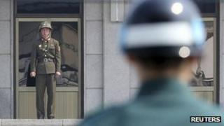 A North Korean soldier (left) and a South Korean soldier keep watch at the truce village of Panmunjom, in the demilitarized zone separating the two Koreas in Paju, north of Seoul, 4 April 2013