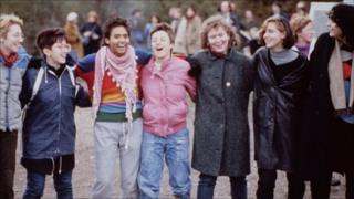Women locking arms and singing at Greenham Common