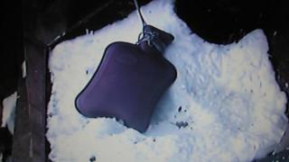 The hot water bottle lying in the snow.