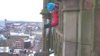 A member of the trust lowers the hot water bottle towards the nest from the tower at Derby Cathedral.