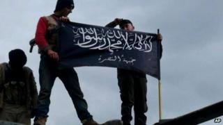 Rebels from the al-Nusra Front waving their brigade flag on the top of a Syrian air force helicopter