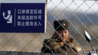 File photo: A soldier stands guard near a barbed wire fence on Hwanggumpyong Island located in the middle of the Yalu River, near the North Korean town of Sinuiju and the Chinese border city of Dandong, 29 March 2013
