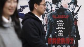 People walk past a Django Unchained poster in Beijing