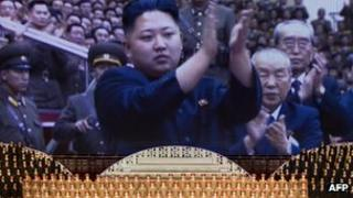 North Korean performers sit beneath a screen showing images of leader Kim Jong-Un at a theatre during celebrations to mark the 100th birth anniversary of the country's founding leader Kim Il-Sung, in Pyongyang on 16 April 2012.