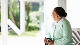 An elderly woman looking wistfully out of a window