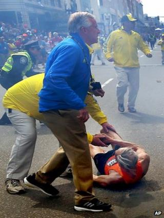 Officials help a runner who fell following the blast at the marathon in Boston on 15 April 2013