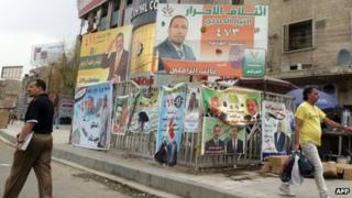 Iraqi men walk past provincial elections campaign poster in Baghdad