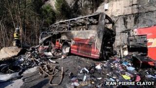 Firefighter stands near bus wreckage