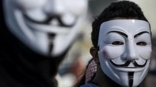 Two men wearing V for Vendetta masks