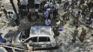 """Police and forensic officials inspect the scene of a blast near the office of India""""s main opposition Bharatiya Janata Party (BJP) in the southern Indian city of Bangalore April 17, 2013."""