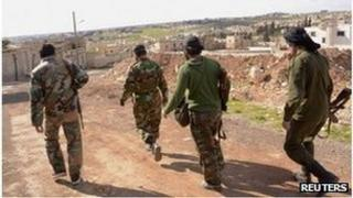 Syrian soldiers walk near scene of alleged chemical weapons attack in Khan al-Assal (23/03/13)