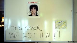 """Sign in hotel lobby with photo of Dzhokhar Tsarnaev with caption """"It's over, we got him"""""""