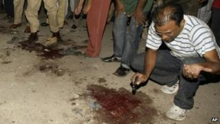 Police gather at the site of the attack on the MQM offices in Karachi