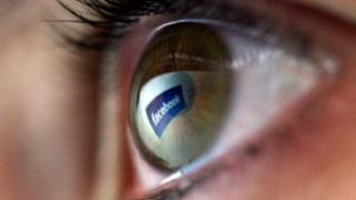 Facebook logo reflected in an eye
