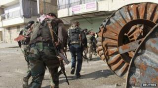 Free Syrian Army fighters carry their weapons as they move towards their positions during an infiltration operation in Aleppo's neighbourhood of Salaheddine