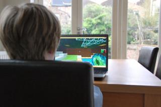 Boy plays Minecraft at kitchen table