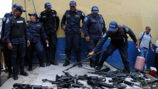 Police officers lay down their weapons during a work stoppage on 23 April 2013