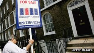 estate agent erects sign