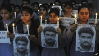 ndian school children hold photographs of Sarabjit Singh, an Indian spy on death row in Pakistan as they light candles and pray for his recovery in Amritsar, India, Monday, April 29, 2013