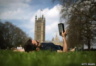 Man reads e-reader lying in grass near Houses of Parliament